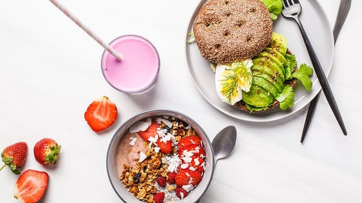 Food on the table. An oatmeal bowl with strawberries, plate with avocado toast and pink fruit smoothie.
