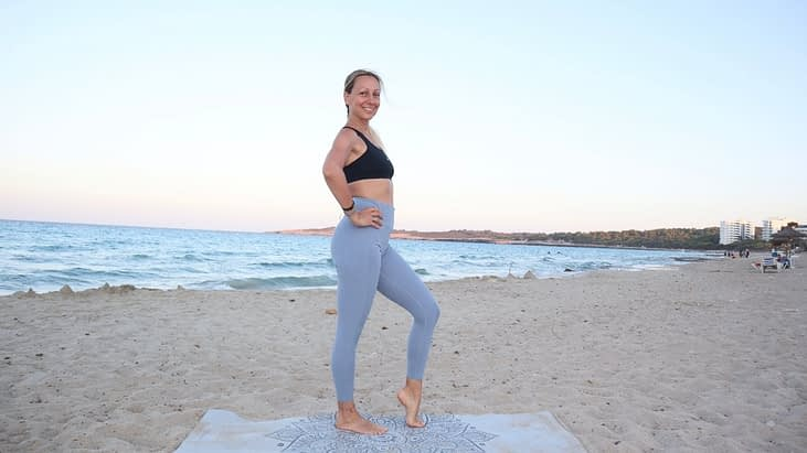 Pilates Instructor standing on the beach in Mallorca, with hand on the hips and one leg front. Smiling. Wearing blue leggings and black top.
