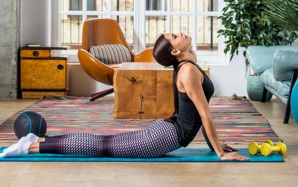 Woman in active wear, motivated for a workout, on the yoga mat, doing a Pilates swan exercise. She is surrounded by different Pilates props: dumbbells, Pilates ball, etc. She exercises in her living room.