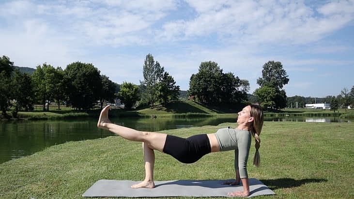 Pilates Instructor in backwards plank kicking with one leg.